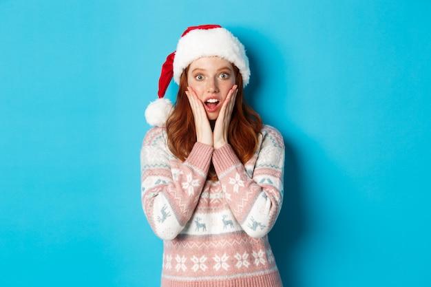 冬とクリスマスイブのコンセプト。サンタの帽子をかぶった感動した赤毛の女の子は、青い背景に立って、驚くべきニュースを聞き、頬に触れ、口を開けて魅了されました。