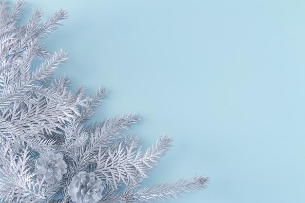 水色の背景の上に、シルバーのクリスマスの装飾の枝と冬とクリスマスのお祭りの背景。