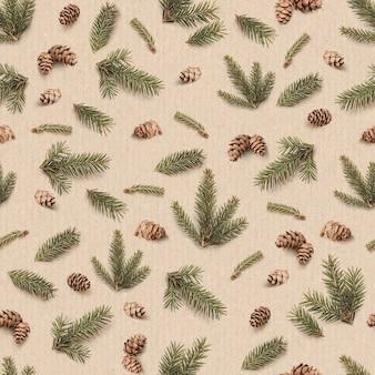茶色のクラフト紙の背景に円錐形とモミの木の枝で作られた冬とクリスマスのシームレスなパターン。