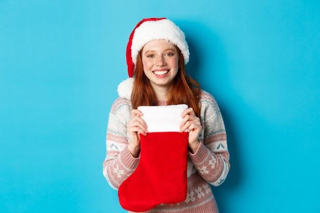 冬と休日のコンセプト。クリスマスの靴下でプレゼントを受け取り、サンタの帽子をかぶって幸せそうに笑って、青い背景の上に立っている陽気な女の子。