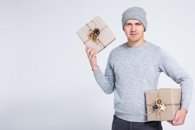 겨울 및 휴일 개념 - 복사 공간이 있는 회색 배경 위에 선물 상자를 들고 포즈를 취한 따뜻한 겨울 옷을 입은 쾌활한 젊은 남자의 초상화