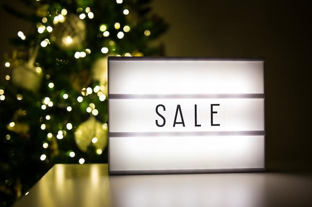冬とショッピングのコンセプト-装飾されたクリスマスツリーと暗い部屋での販売の言葉とlihtbox