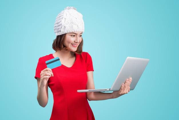 青いビネットに対してラップトップとクレジットカードを保持している冬のアジアの女性