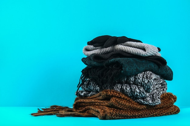 Winter and autumn clothes, hats, scarves, gloves on a blue pastel background.