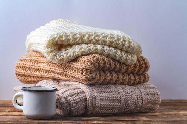 Winter, autumn clothes, knitted scarves and a white mug of hot cocoa