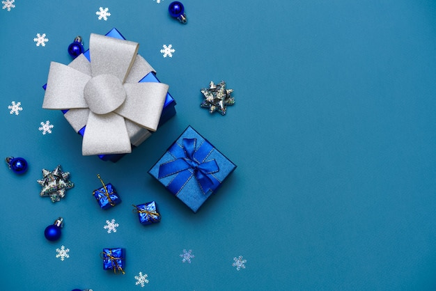 Winter background blue cute gift box with blue ribbon christmas balls in a christmas composition of ...