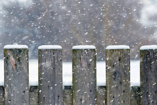 Зимний фон с заснеженным деревянным забором во время снегопада