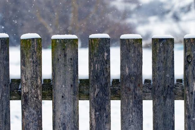 雪に覆われた木製の柵と冬の背景