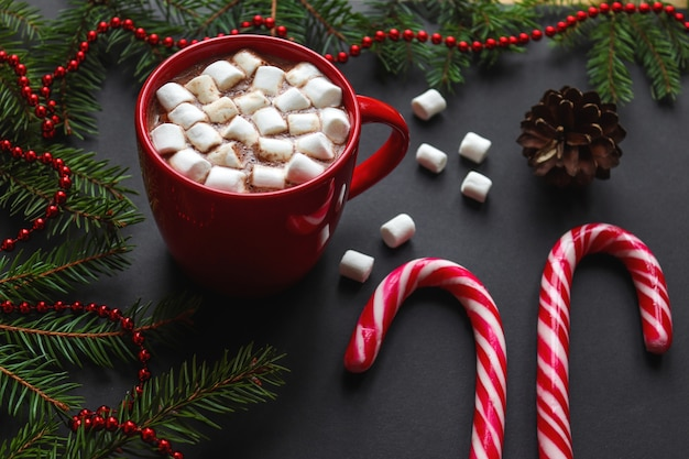 Winter background with christmas tree branches, pine cones, hot chocolate, marshmallows, candy canes