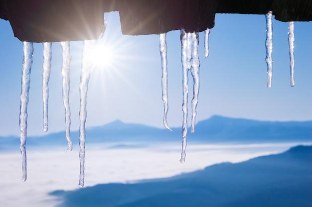 木造住宅の屋根につららと冬の背景。山の村で解凍します。青い空と晴れた天気