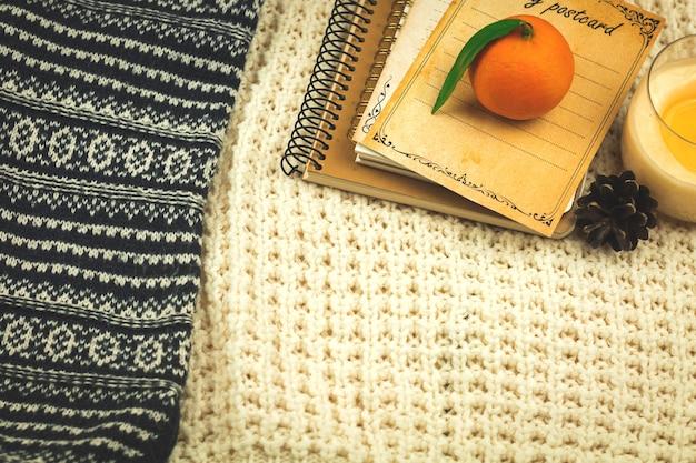 ニットのセーター、本、みかん、居心地の良い休日のホームコンフォートコンセプト、コピースペースの写真と冬の背景
