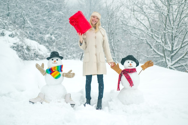 Winter background with snowflakes and snowman girl playing with snowman in winter park winter woman