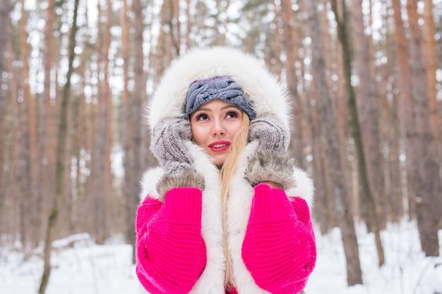 Концепция зимы, красоты и моды - портрет молодой блондинки в шубе на снежной природе