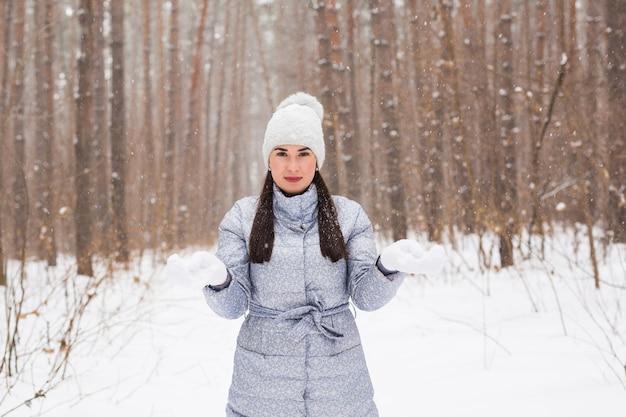 Концепция зимы, красоты и моды - портрет молодой женщины в пальто на стене снежной природы