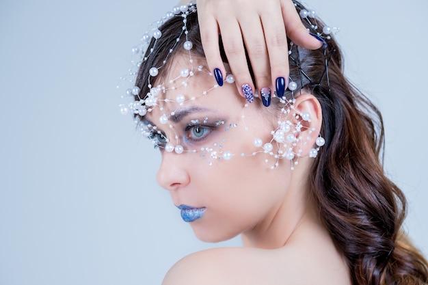 冬の美しさ。雪髪スタイルとメイクアップと美しいファッションモデルの女の子。休日の化粧とマニキュア。雪と氷の髪型と冬の女王