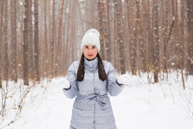 Winter, beauty and fashion concept - portrait of young woman in coat at snowy nature wall