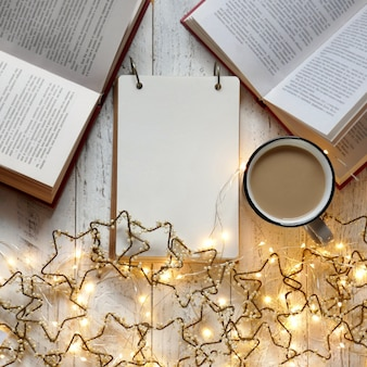 Winter books. winter cozy reading.to do list on winter holidays. shopping list cup of tea and luminous garland.winter . plans for christmas.blank notepad and luminous garland