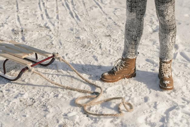 ロープでそりの近くの雪の上の冬のブーツ。