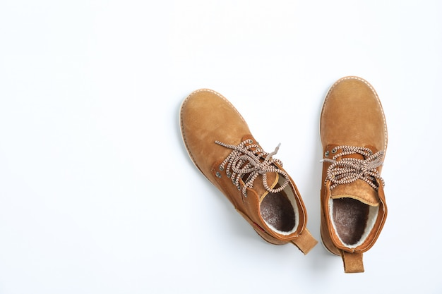 Winter boots on white background, top view