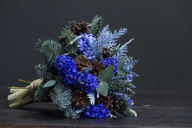 Winter bouquet of nobil fir twigs, blue hyacinths and cones, winter gift concept