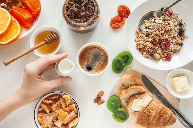 Зимний завтрак с мюсли из сухофруктов и цукатами на белом столе. женская рука держит молочника за чашкой свежего кофе. вид сверху. фото высокого качества