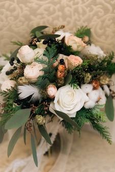 バラ、トウヒ、綿、黒い果実、羽、素朴なドライフラワーのパステルカラーの冬の花嫁の花束。セレクティブフォーカス