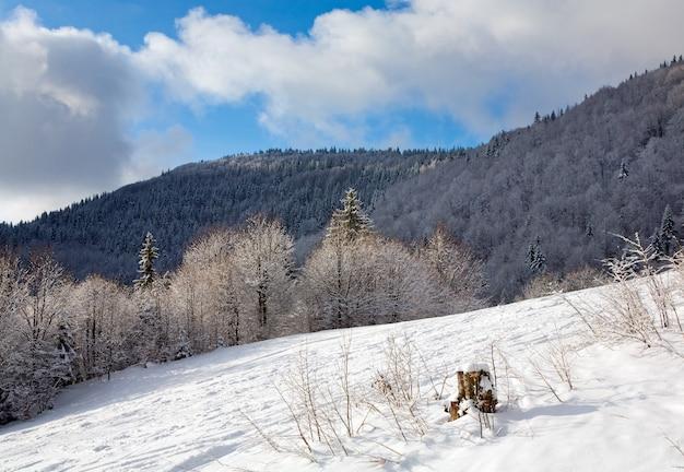 Зимний спокойный горный пейзаж с инеем и заснеженным лесом и горнолыжным спуском