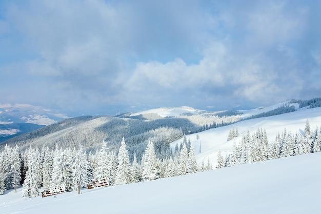 Зимний спокойный горный пейзаж с навесами и горным хребтом позади (гора куколь, карпаты, украина)