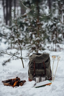 Winter camping. bonfire with travel rucksack, map, two mug and marshmallow on snow