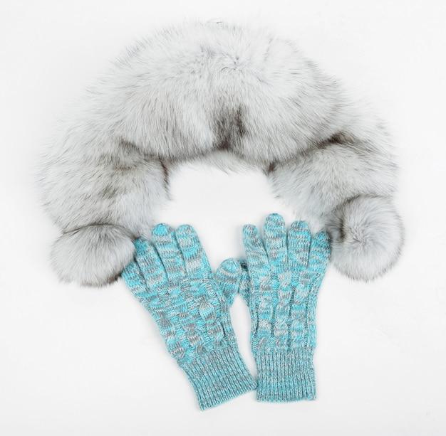 Зимняя шапка и варежки, изолированные на белой поверхности
