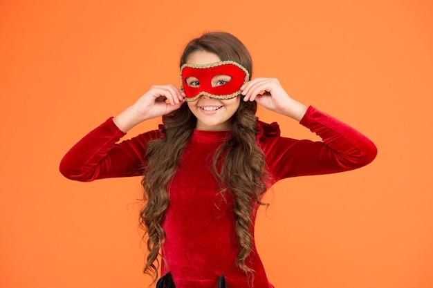 겨울 카니발. 시크릿 모드. 아이는 아이 마스크를 착용합니다. 소녀는 마스크 오렌지 배경을 착용합니다. 겨울 이벤트 및 엔터테인먼트. 아동 발달. 익명으로 공개 이벤트를 방문하십시오. 겨울 신년 파티입니다.