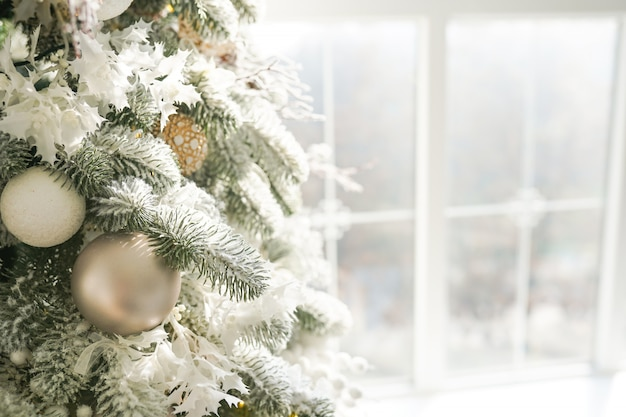 Winter celebration background, christmas tree near window at home. copy space