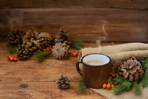 겨울, 소박한 스타일의 크리스마스 배경입니다. 따뜻한 밀크티가 든 금속 빈티지 머그는 소나무 콘, 가문비나무 가지, 로즈힙 사이의 나무 표면에 있는 식탁보 위에 있습니다. 복사 공간, 플랫 레이