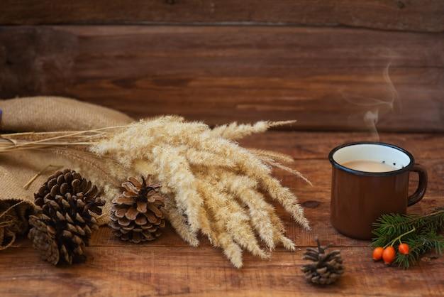 겨울, 소박한 스타일의 크리스마스 배경입니다. 뜨거운 우유 차가 있는 금속 빈티지 머그가 식탁보에 서 있습니다.