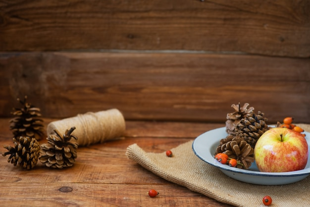 겨울, 소박한 스타일의 크리스마스 배경입니다. 사과와 솔방울이 있는 빈티지 금속 그릇이 나무 표면에 서 있습니다. 복사 공간, 플랫 레이