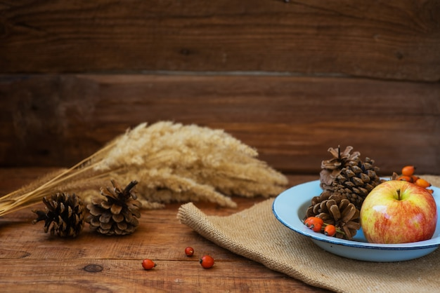 겨울, 소박한 스타일의 크리스마스 배경입니다. 사과와 솔방울이 있는 빈티지 금속 그릇
