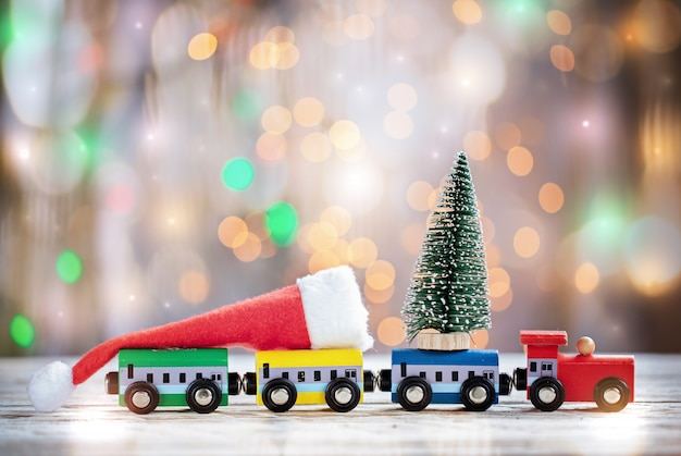 Winter christmas background miniature colorful train with fir tree. holiday greeting card.