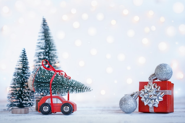 Winter christmas background miniature red car with fir tree. holiday greeting card.