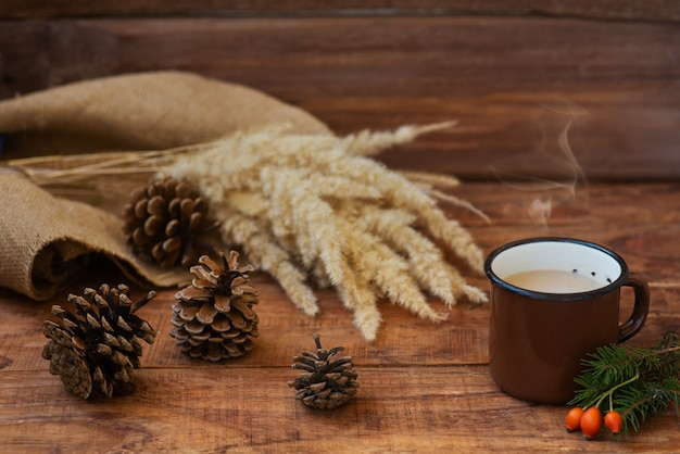 Winter, christmas background in rustic style. a metal vintage mug with hot milk tea stands on a tablecloth