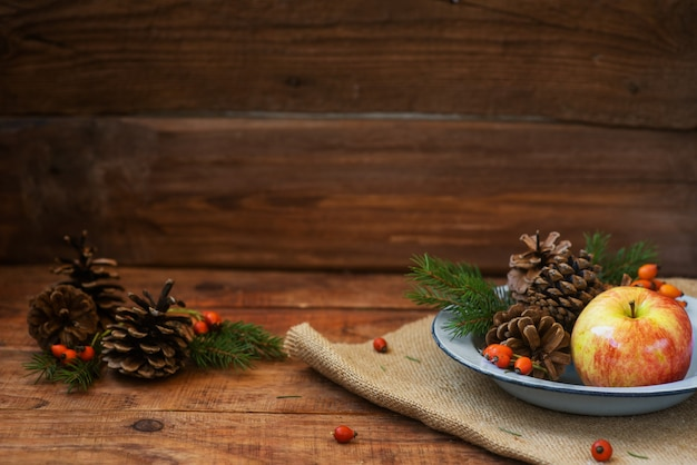 Winter, christmas background in rustic style. a vintage, metal bowl with an apple and pine cones