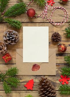 空白のカードと木製のテーブルの上の封筒と冬のクリスマスの構成は平らに横たわっていた