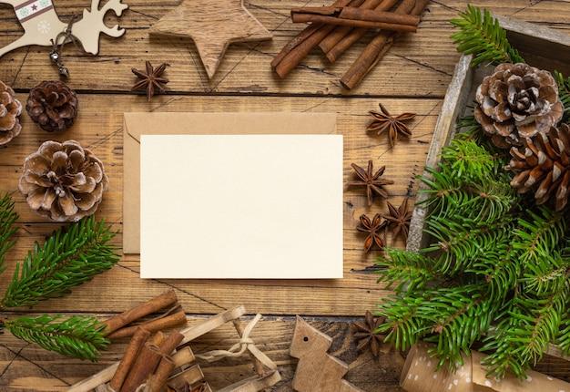 Зимняя рождественская композиция с пустой картой, конвертом, специями, еловыми ветками и украшениями на деревянном столе. рождество и новый год шаблон поздравительной открытки вид сверху. праздничный макет