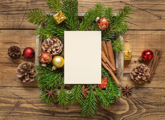 Зимняя рождественская композиция с пустой карточкой, еловыми ветками и украшениями на деревянном столе. рождество и новый год шаблон поздравительной открытки вид сверху. праздничный макет