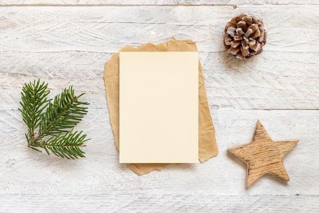 モミの枝、木の星、松ぼっくりの平らな場所の近くにカードを置いた冬のクリスマスの作曲。白い木製の背景の上面図にクリスマスと新年のグリーティングカードテンプレート。休日のモックアップ。