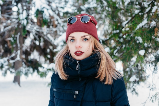 Winter, christmas, emotions, people, lifestyle and beauty concept- christmas girl outdoor portrait. winter woman blowing snow in a park. flying snowflakes. sunny day. backlit. good mood