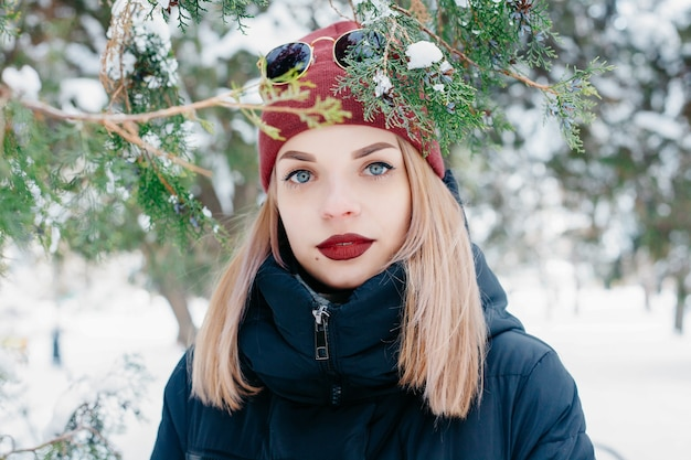 Winter, christmas, emotions, people, lifestyle and beauty concept- christmas girl outdoor portrait. winter woman blowing snow in a park. flying snowflakes. sunny day. good mood