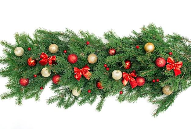 緑のモミの枝、弓、赤と金のクリスマスボール、白い背景で隔離のベリーと冬のクリスマスの花輪ボーダーバナー。