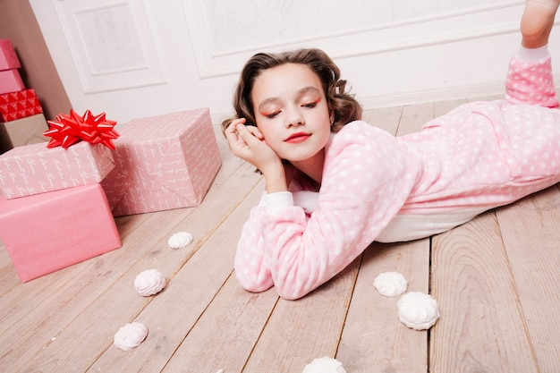 Winter, christmas, holiday, sweets, birthday, celebration and children concept- cute little girl pajama with sweets sitting on the floor, happy childhood concept. girl gifts, soft dog, soap bubbles.