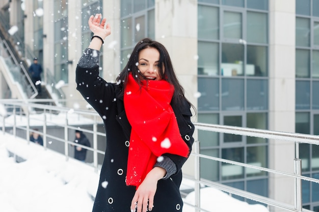 Winter, christmas, lifestyle, holidays and fashion concept - pretty young smiling woman in black coat and red scarf posing in winter city. snowing