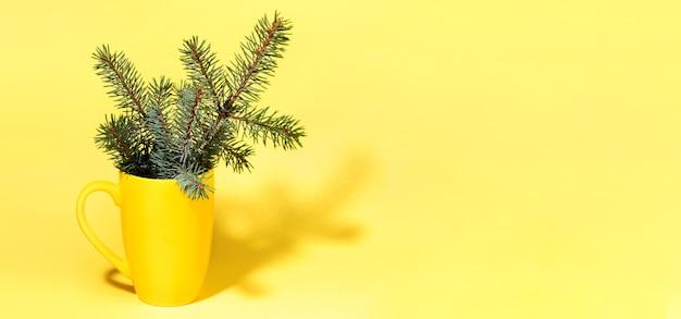 影付きマグカップの新鮮な緑のモミの小枝と黄色の冬のクリスマスの最小限のバナー。